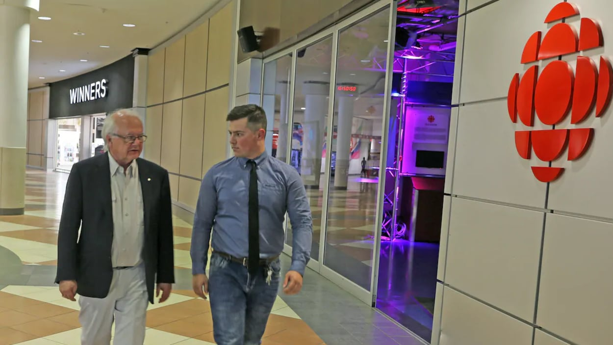 Deux hommes déambulent sur le plancher carrelé d'un centre commercial.