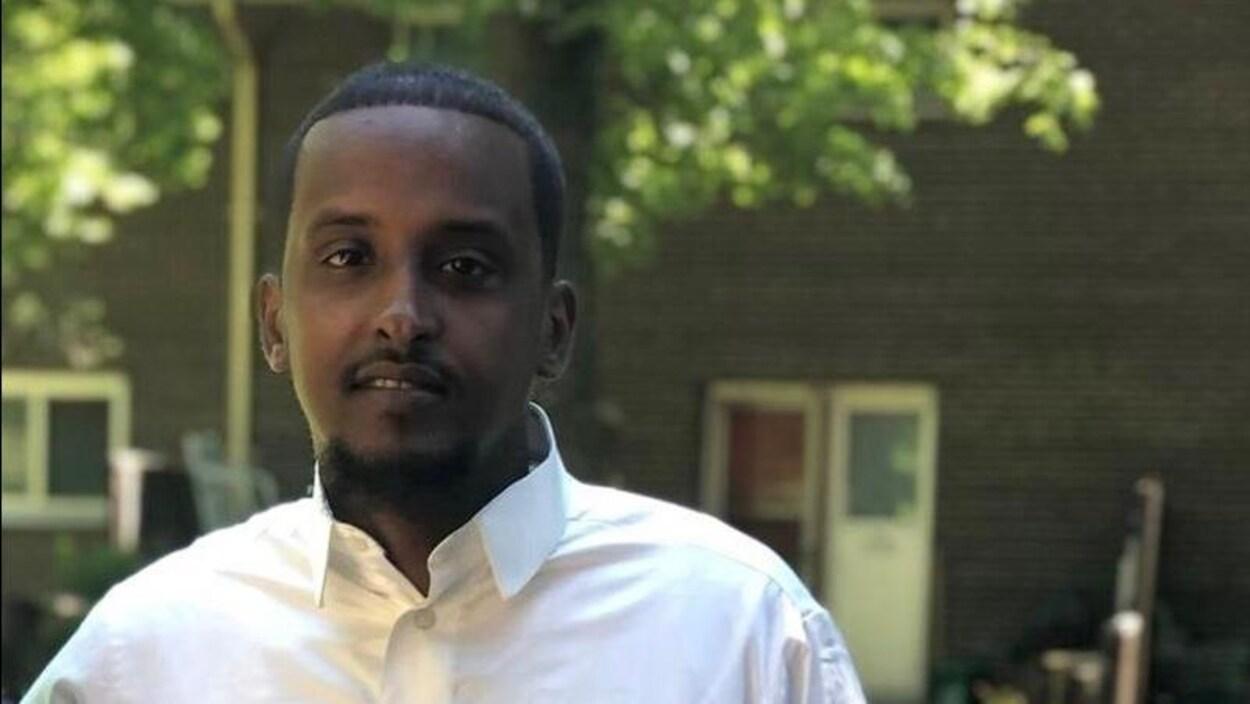 Un homme noire pose pour la photo dans un habit blanc.