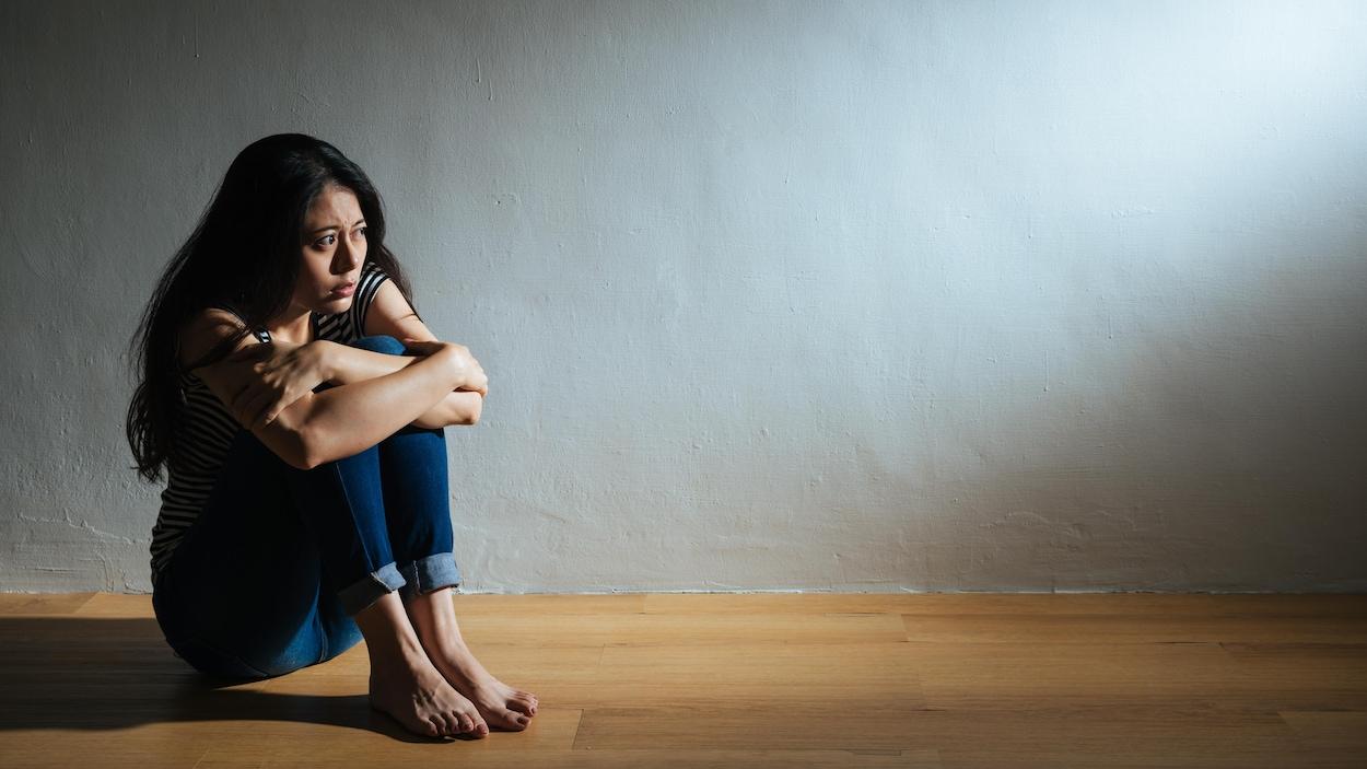 Une femme assise sur le sol dans une pièce vide se tient les genoux.