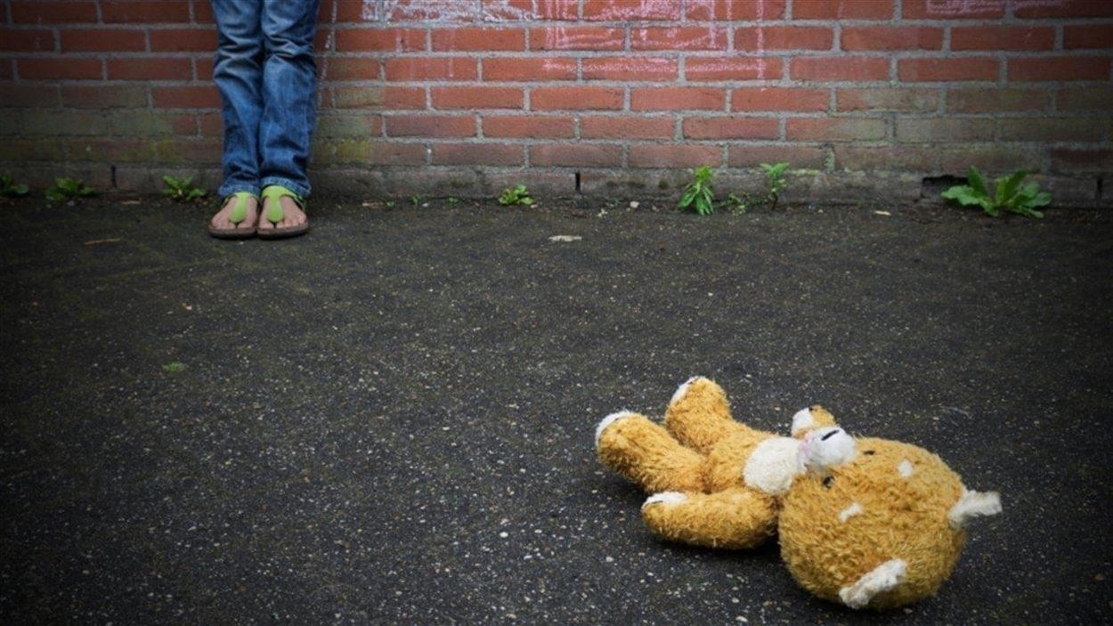 Un ours en peluche est au sol devant un enfant que l'on voit partiellement.