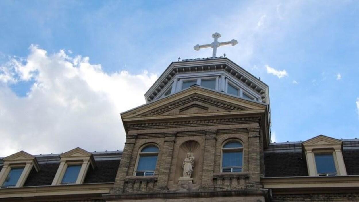 Le sommet d'un édifice avec une statue de la Vierge à l'engfant et une croix surplombant le toit.