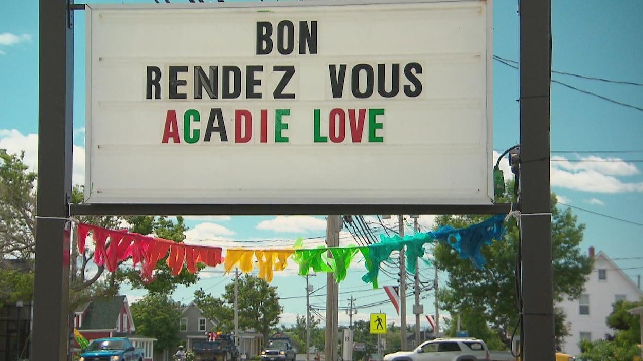 Une affiche aux couleurs de l'arc-en-ciel (drapeau de la fierté) souhaitant un bon Acadie Love à tous.