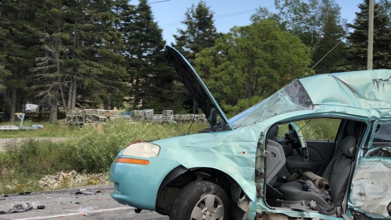 Un véhicule endommagé est immobilisé sur la route, le capot est ouvert. Le pare-brise est brisé en plusieurs morceaux.