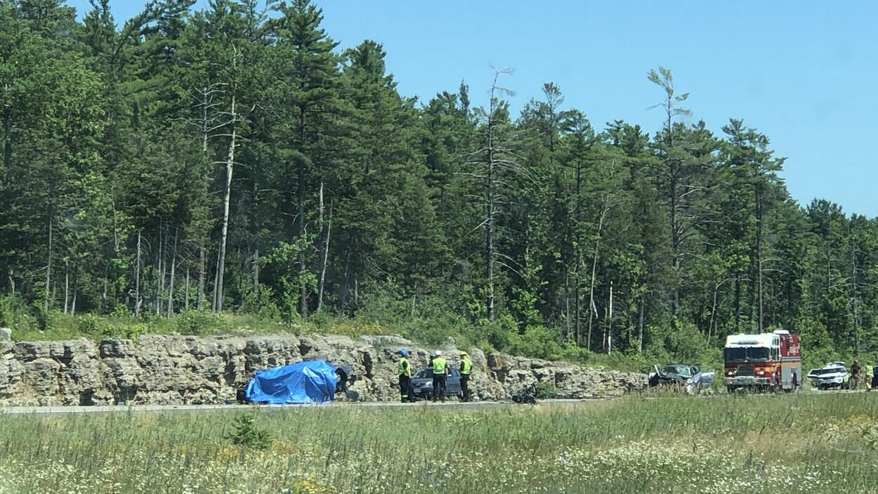 De premiers répondants près d'un véhicule renversé, d'une voiture endommagée et d'un camion de pompier sur l'autoroute 417.