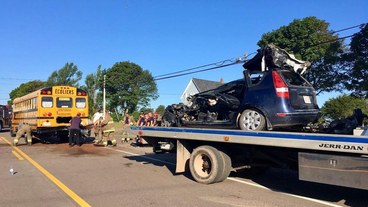 Des pompiers et policiers examinent l'autobus scolaire tandis que la carcasse de la voiture est remorquée.