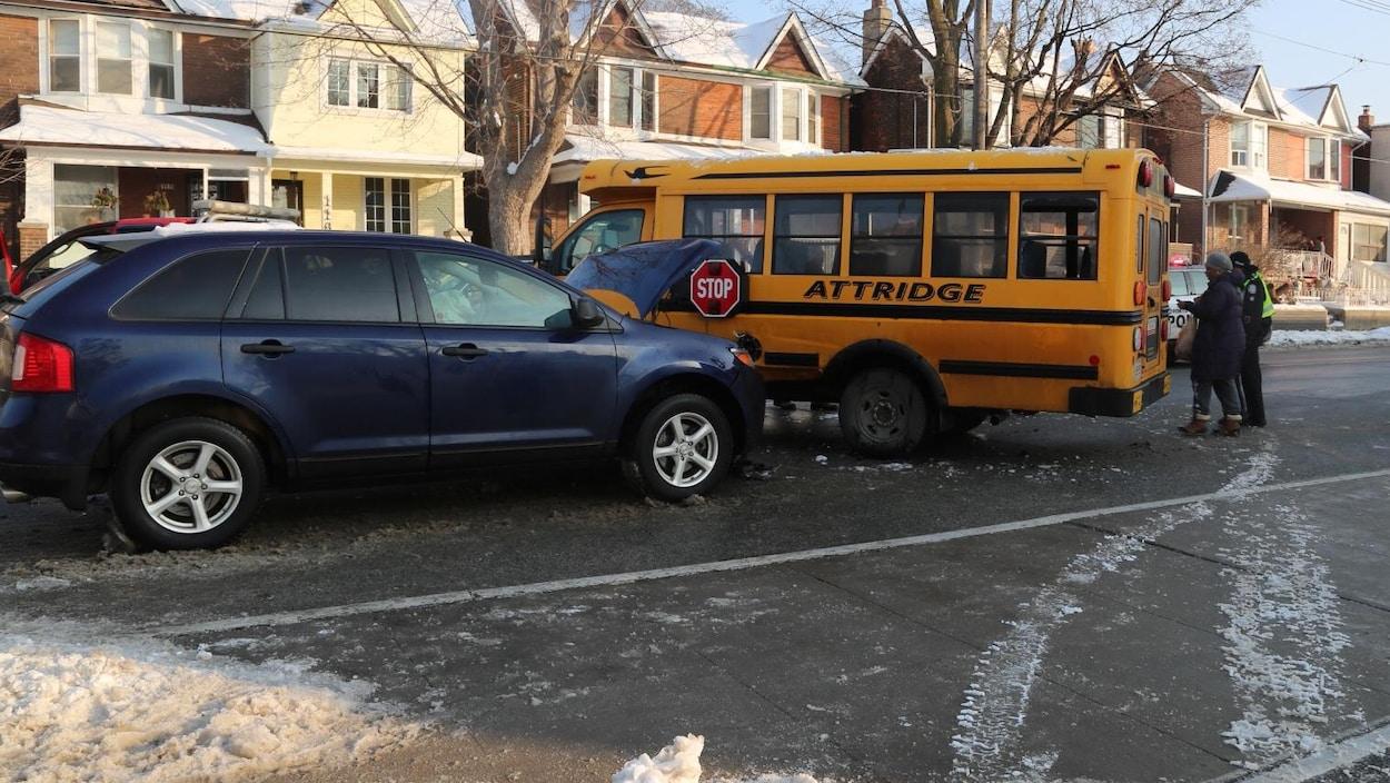 Photo montrant un VUS bleu, le capot ouvert, qui a percuté un petit autobus scolaire jaune en travers de la rue.