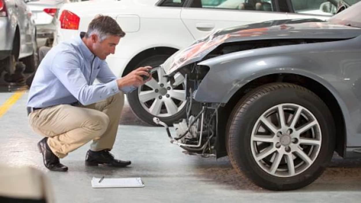 Un homme examine une voiture accidentée