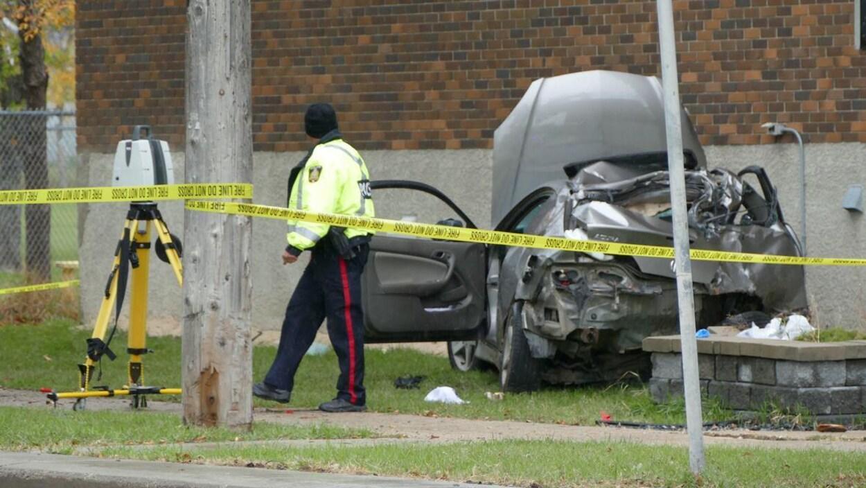Un policier marche devant les restes d'une voiture pratiquement détruite qui repose contre un mur.
