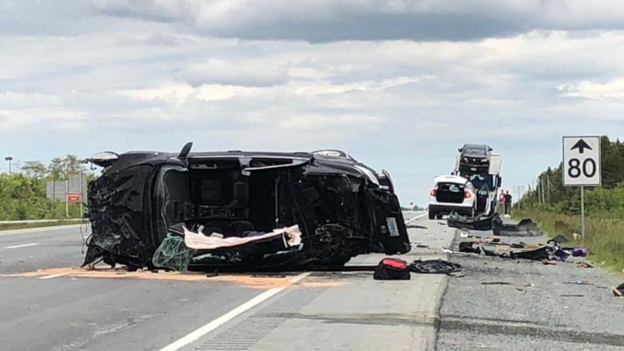 Véhicule accidenté couché sur le côté en travers de l'autoroute.