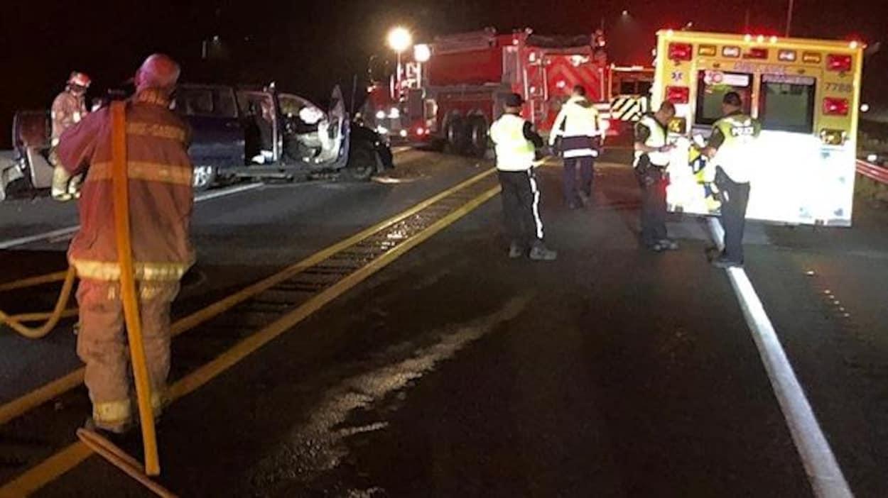 Des pompiers, ambulanciers et policiers entourent un des véhicules accidentés.