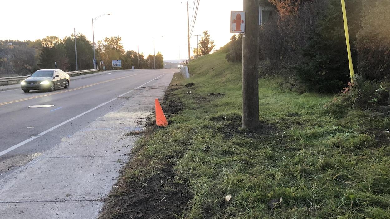Un cône orange et un poteau d'électricité en bordure du boulevard Saguenay.