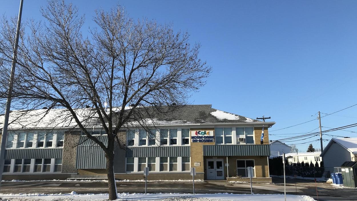 Un bâtiment avec l'inscription «École Notre-Dame-du-Rosaire».