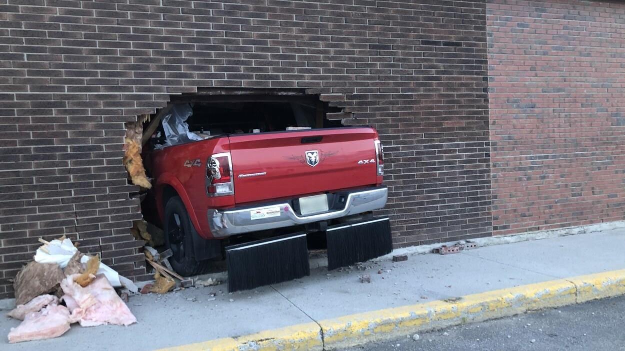 Un camion dans un mur de briques.
