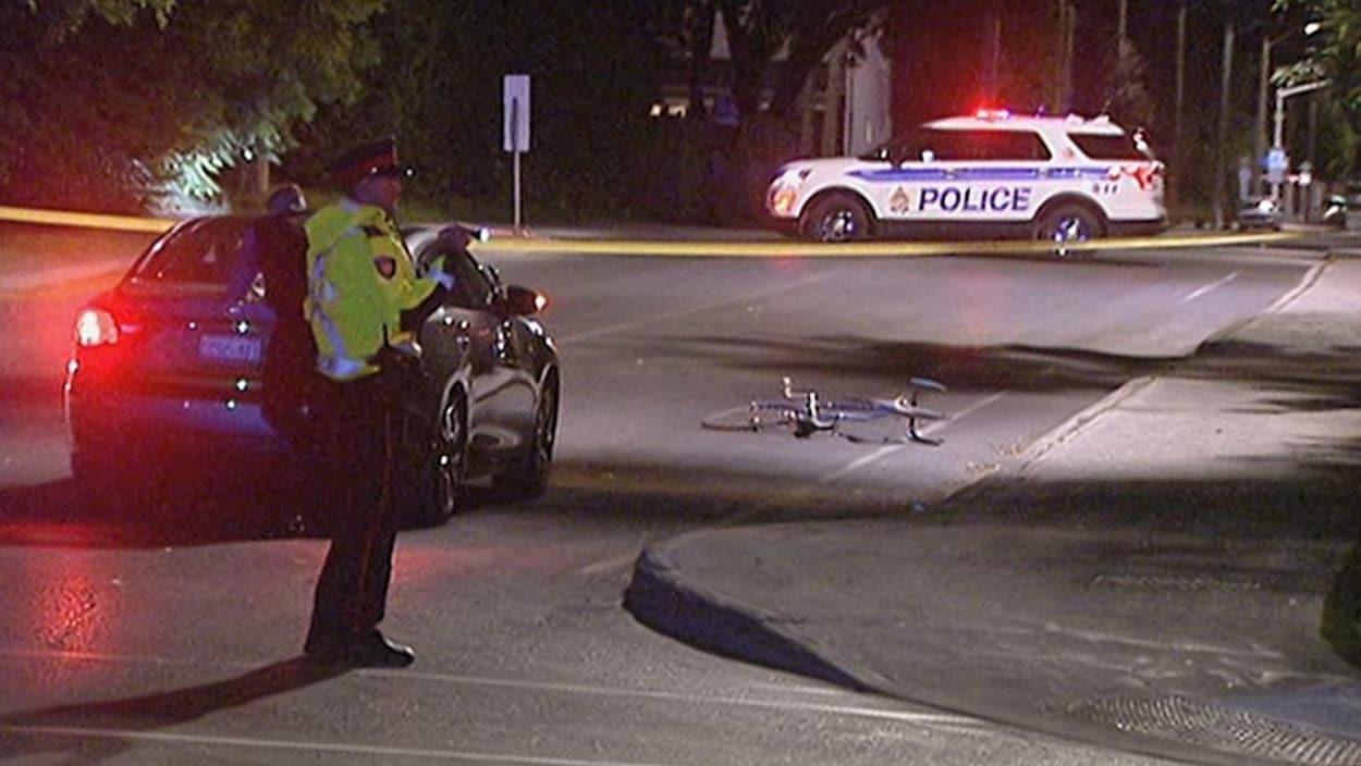 Un policier est à proximité du véhicule et du vélo percuté.