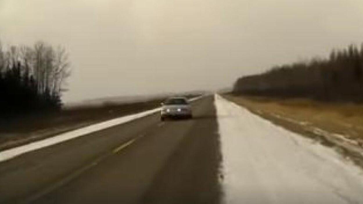 Une voiture roule sur une route.