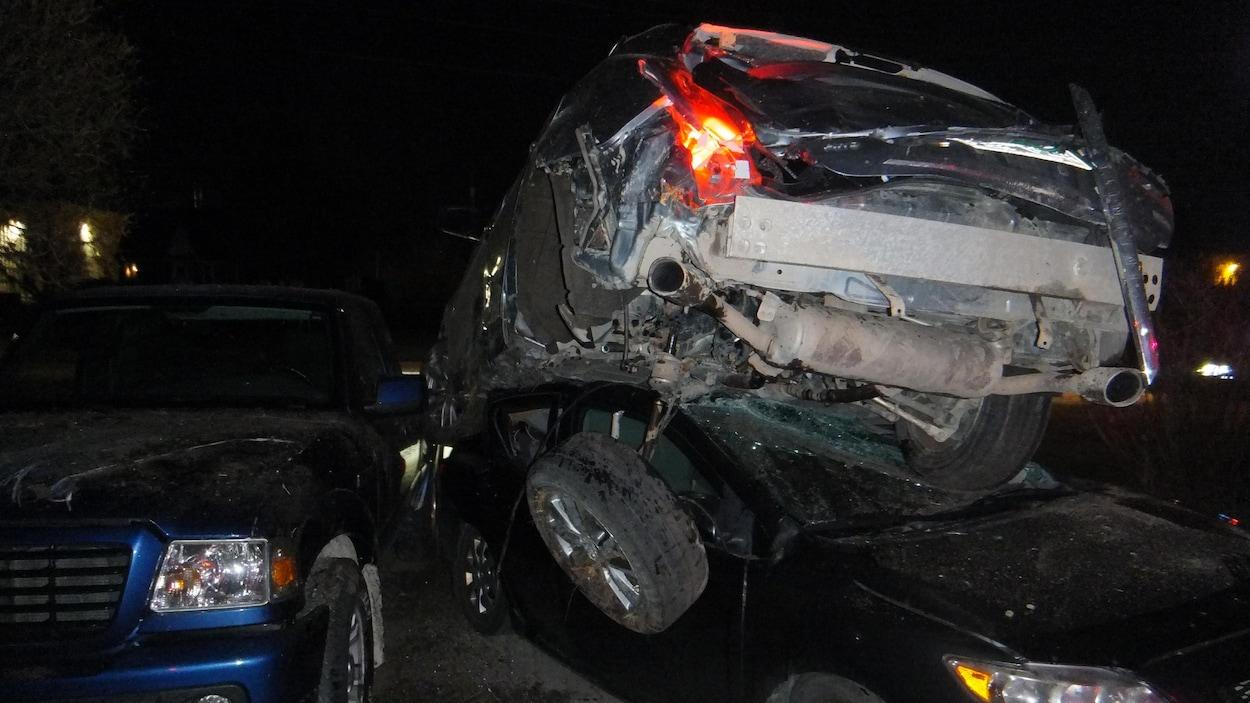Une voiture accidentée a terminé sa course sur une autre voiture stationnée.