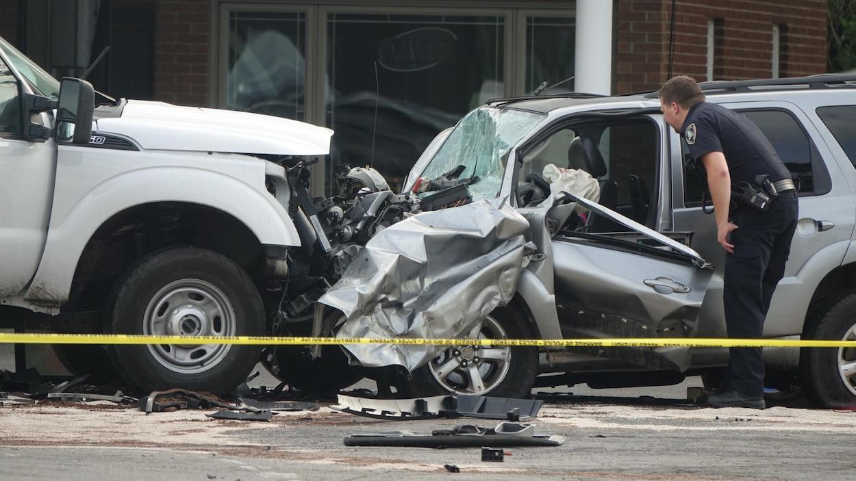 Une camionnette et une voiture lourdement endommagée sur la scène d'une collision frontale à L'Assomption, dans Lanaudière. Un policier regarde à l'intérieur de la voiture accidentée.