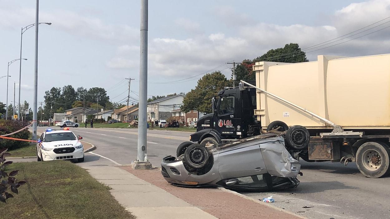 Une voiture compact renversée, dont la partie arrière est lourdement endommagée. Près de cette voiture sont stationnés un camion d'ordures et une voiture du Service de police de la Ville de Gatineau.