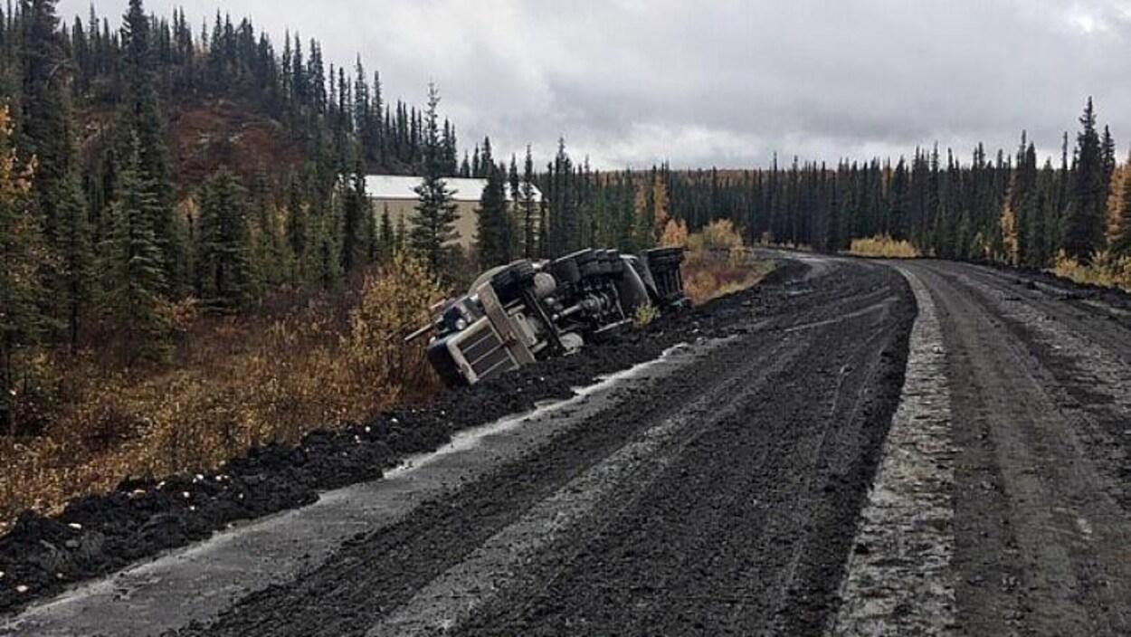 Une route en mauvais état et un camion renversé du côté gauche.
