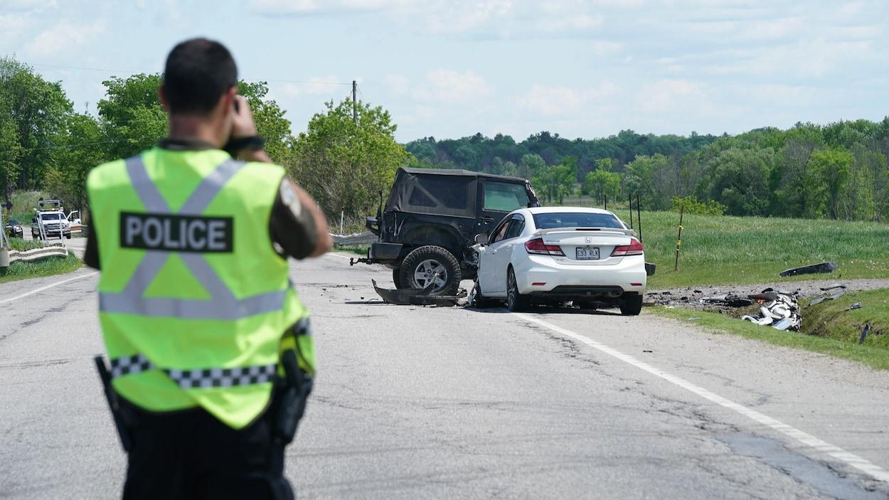 Un policier prend une photo des deux voitures impliquées dans la collision.