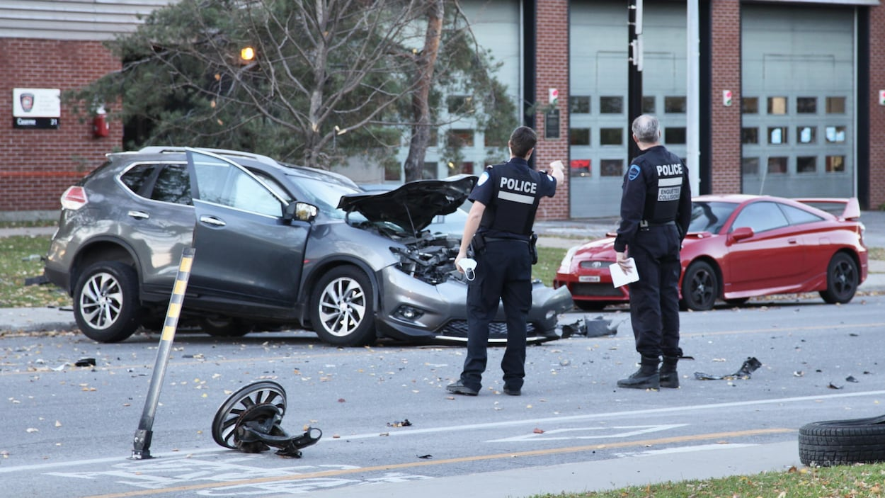 Deux policiers du SPVM se parlent près de la camionnette accidentée.