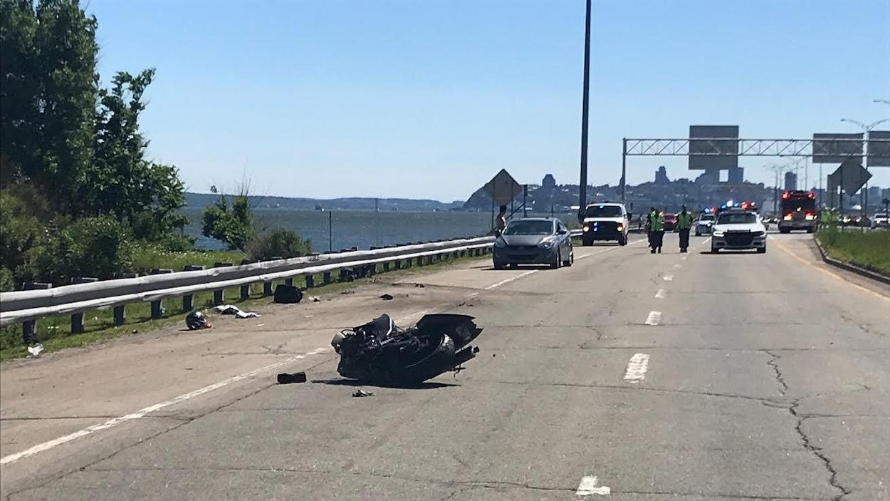 Scène de l'accident. On aperçoit la moto accidentée, couchée sur le côté. À l'arrière-plan, on distingue des véhicules d'urgence stationnés sur la voie est de l'autoroute Dufferin-Montmorency, laquelle est bordée par le fleuve Saint-Laurent. Au loin se profile le centre-ville de Québec.