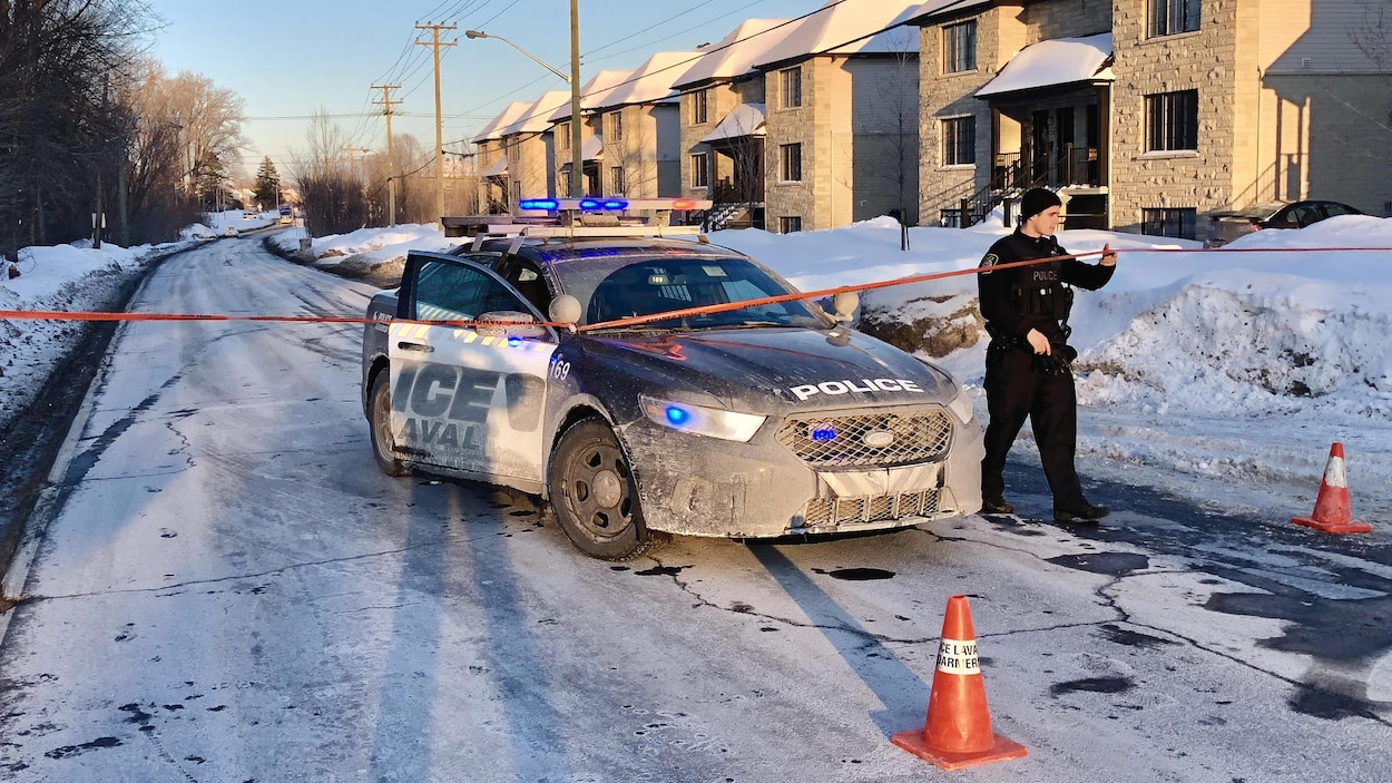 Une voiture de police immobilisée dans une rue, un policier s'apprête à traverser un cordon de sécurité.