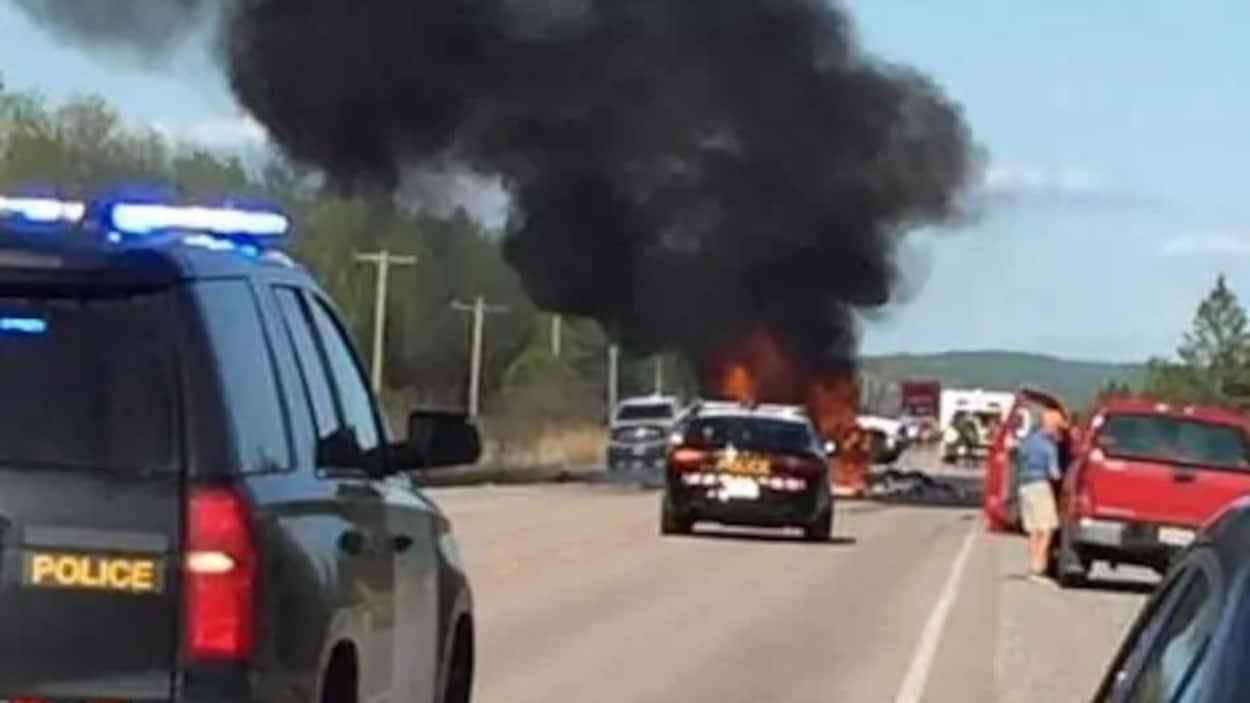 Des voitures de polices près d'un véhicule en feu.