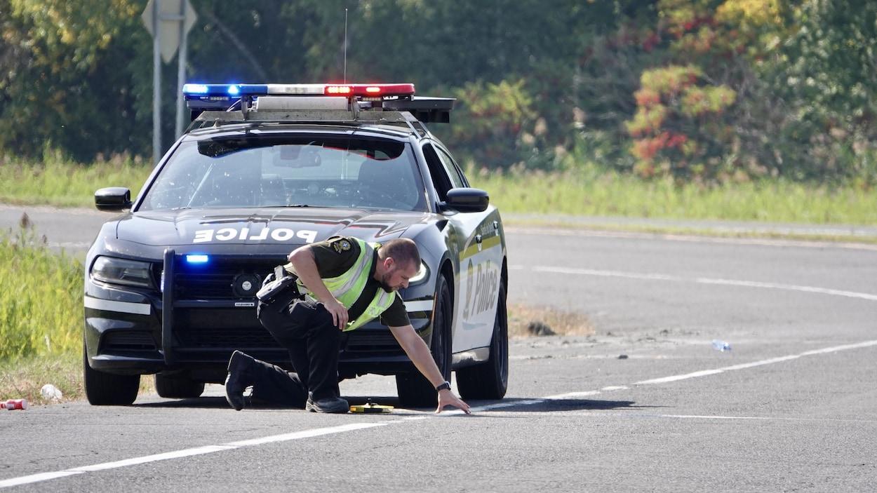 Un policier examine des traces sur la route après un accident.