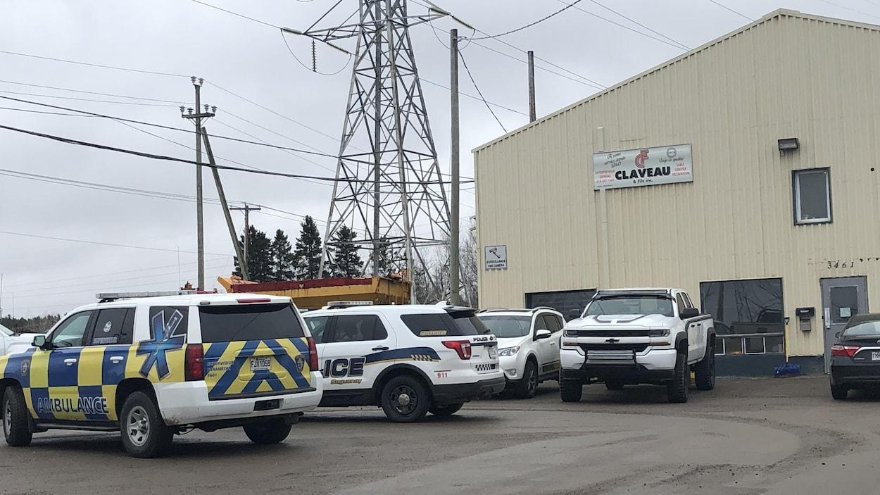 Une voiture de police et une voiture-ambulance dans le stationnement de l'entreprise.