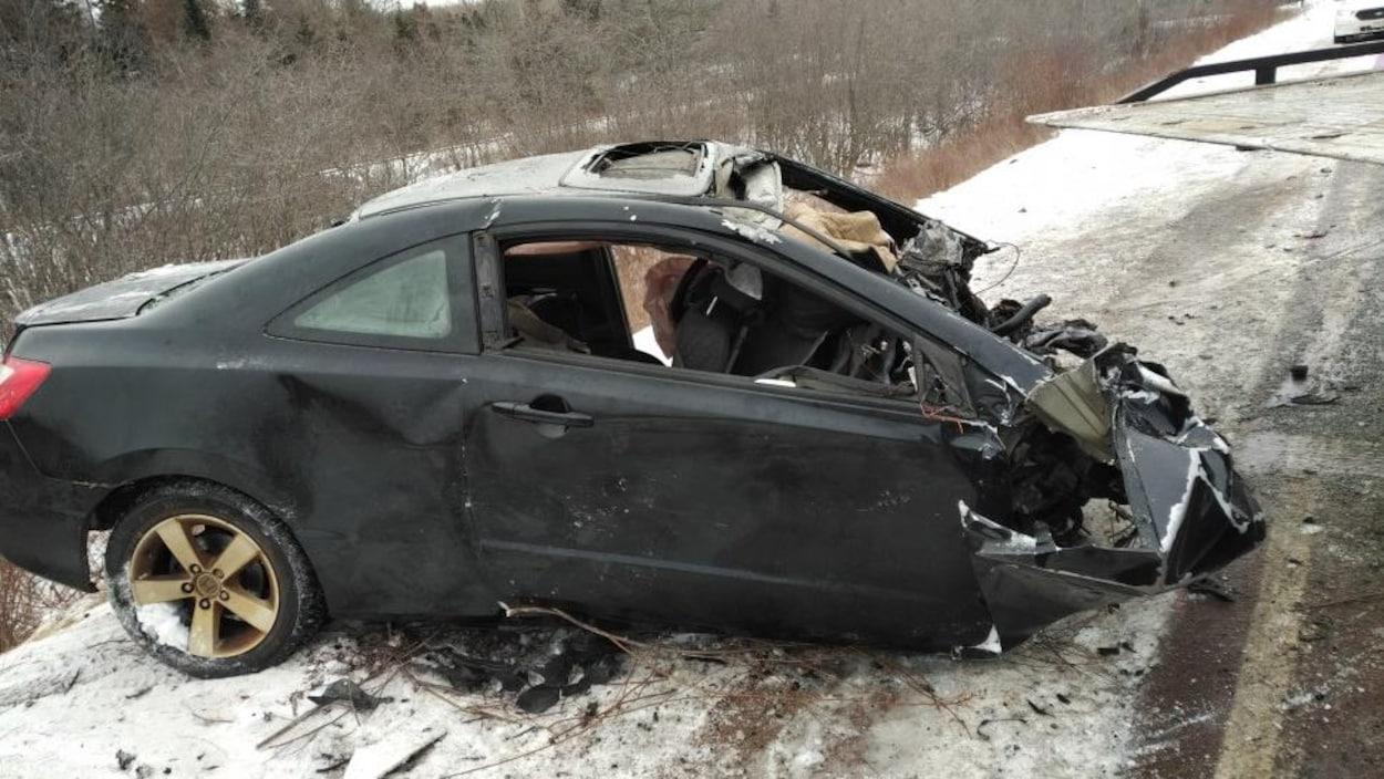 La voiture noire après l'accident, une perte totale.