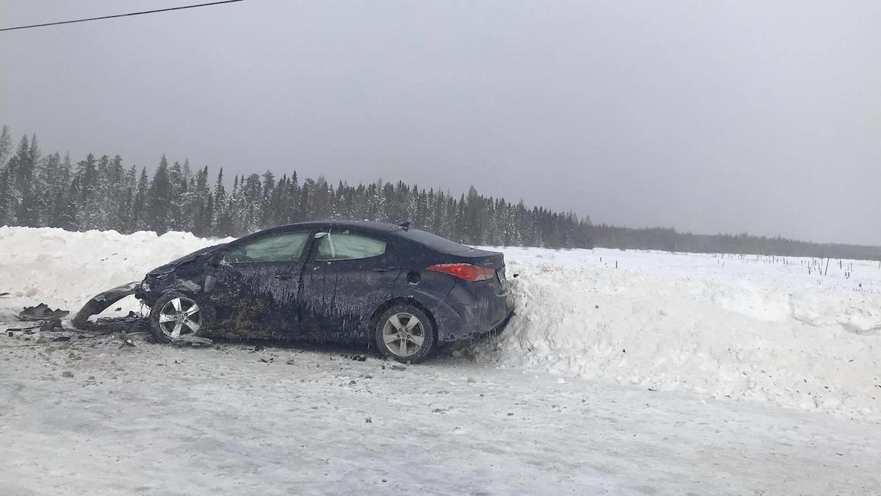 Une voiture avec le capot démoli est sur le bord de la route.