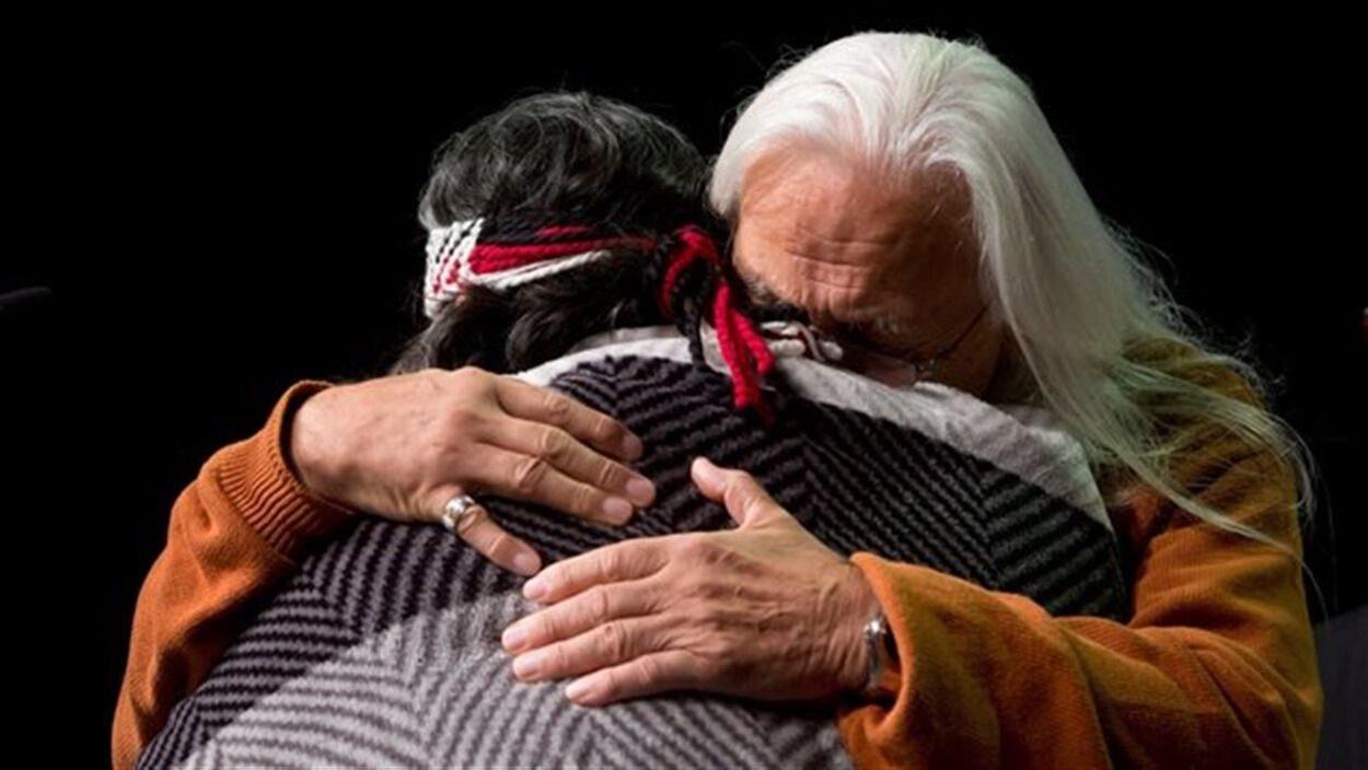 Deux survivants des pensionnats autochtones s'étreignent lors d'un événement de la Commission de vérité et réconciliation du Canada à Vancouver.