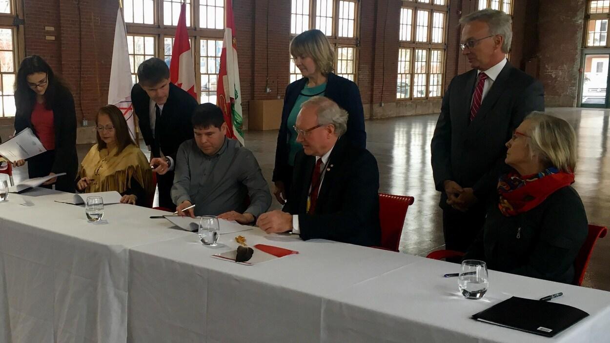 Des femmes et des hommes assis à une table signent un document.