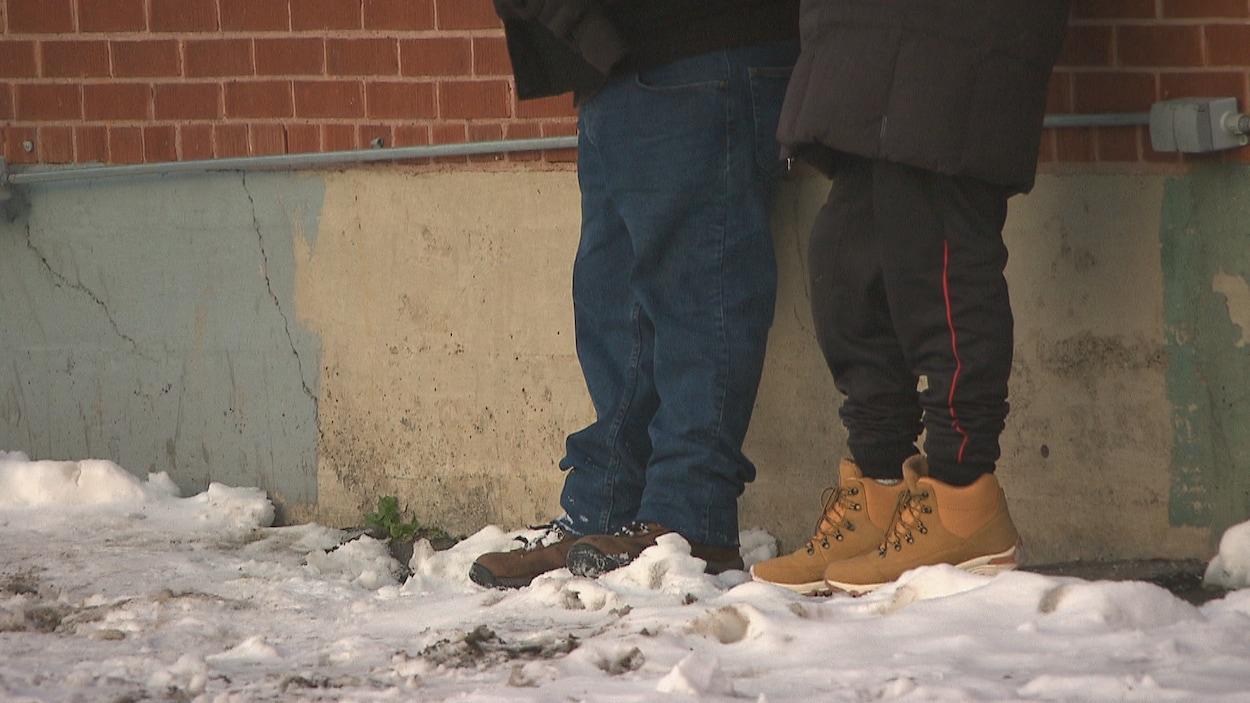 Les pieds de deux personnes dans la neige.