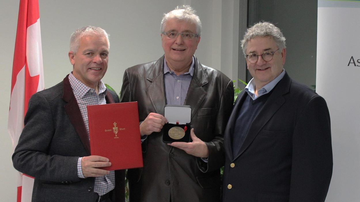 Trois hommes prennent la pose aux côtés d'un drapeau du Canada. L'un d'eux tient une médaille du Sénat qu'il s'est vu décerner.