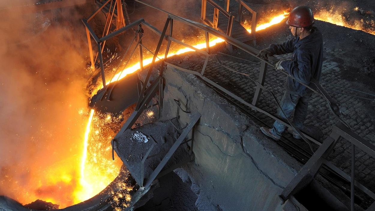 Un travailleur surveille l'écoulement de fer en fusion.