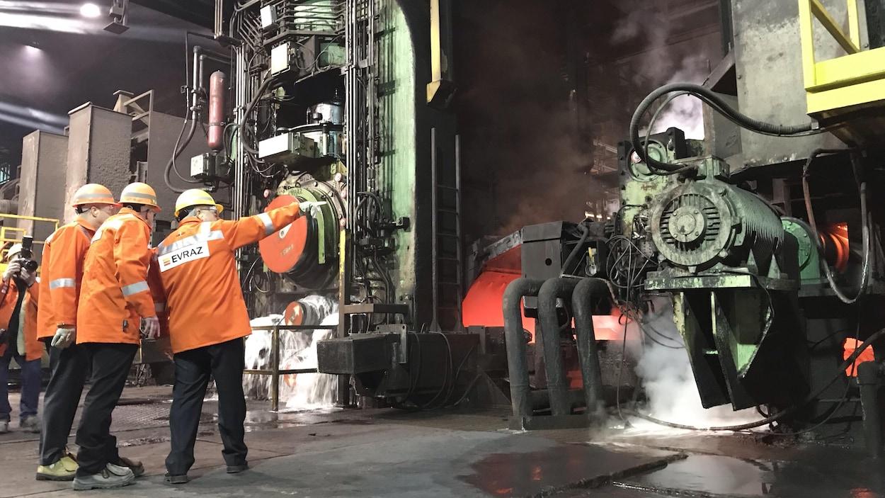 Trois personnes avec des vestes oranges regardent de la machinerie.