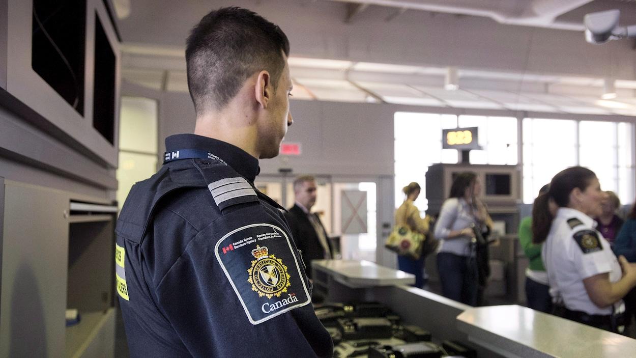 Un douanier canadien regarde des voyageurs.