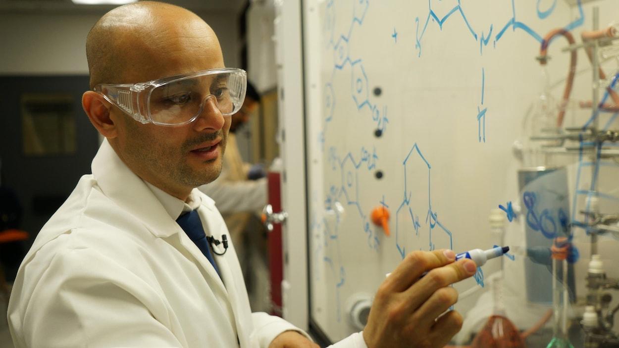 Adam Duong, vêtu d'un sarrau et de lunettes de protection, écrit avec un marqueur sur une vitre.