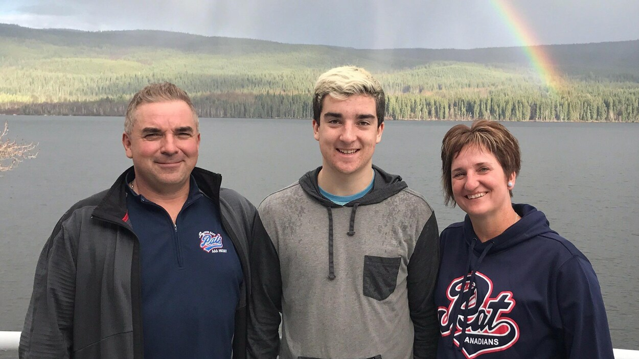 Adam Herold pose avec ses parents Russell et Raelene Herold, devant un lac.