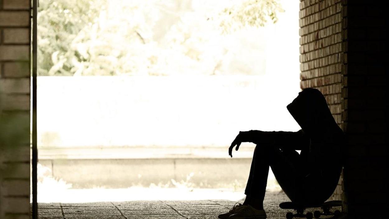 Silhouette d'un jeune assis sur une plance à roulette.