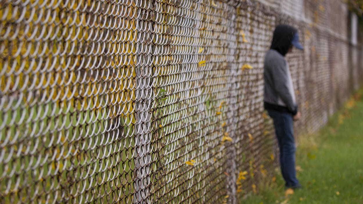 Un adolescent appuyé contre une clôture.