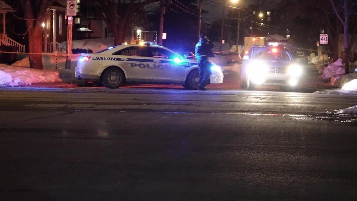 Une voiture de police et un policier au téléphone, à Laval, le 21 janvier 2017.