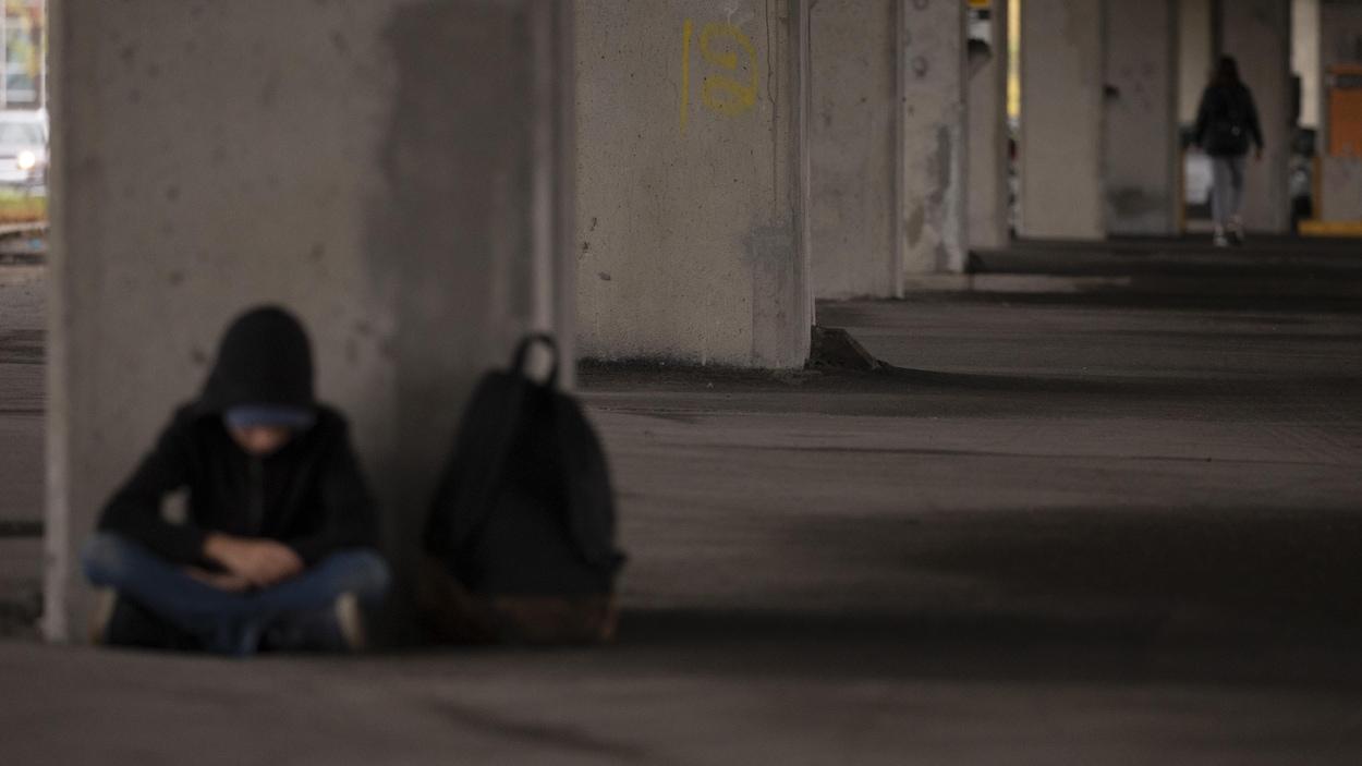 Un jeune adolescent est accroupi dans un stationnement désert. Au loin une jeune femme marche.