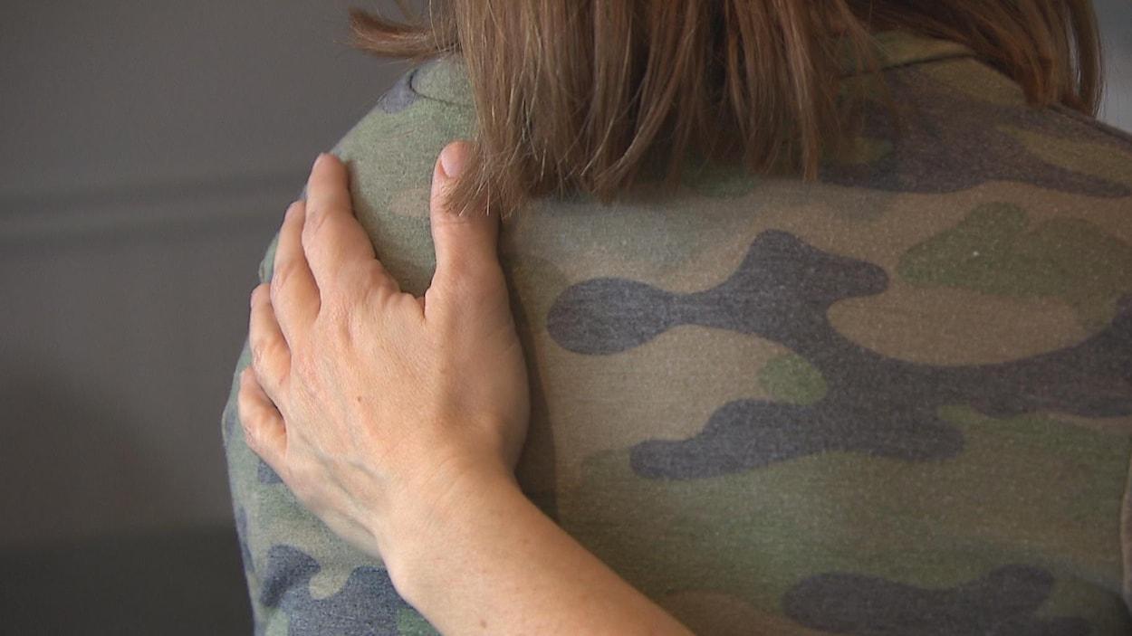 Une main sur le dos d'une jeune fille.