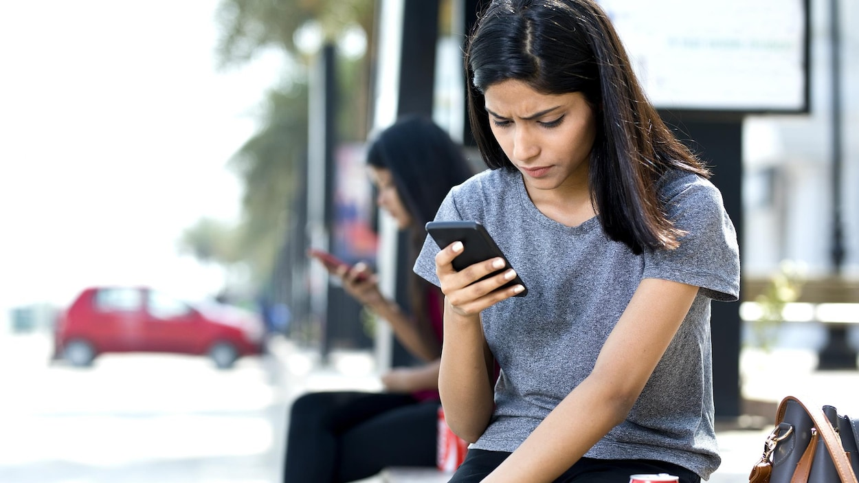 Une jeune femme consulte son téléphone portable.