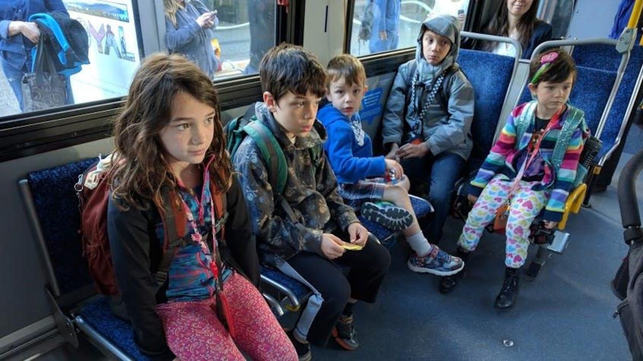 Cinq enfants assis dans un autobus.