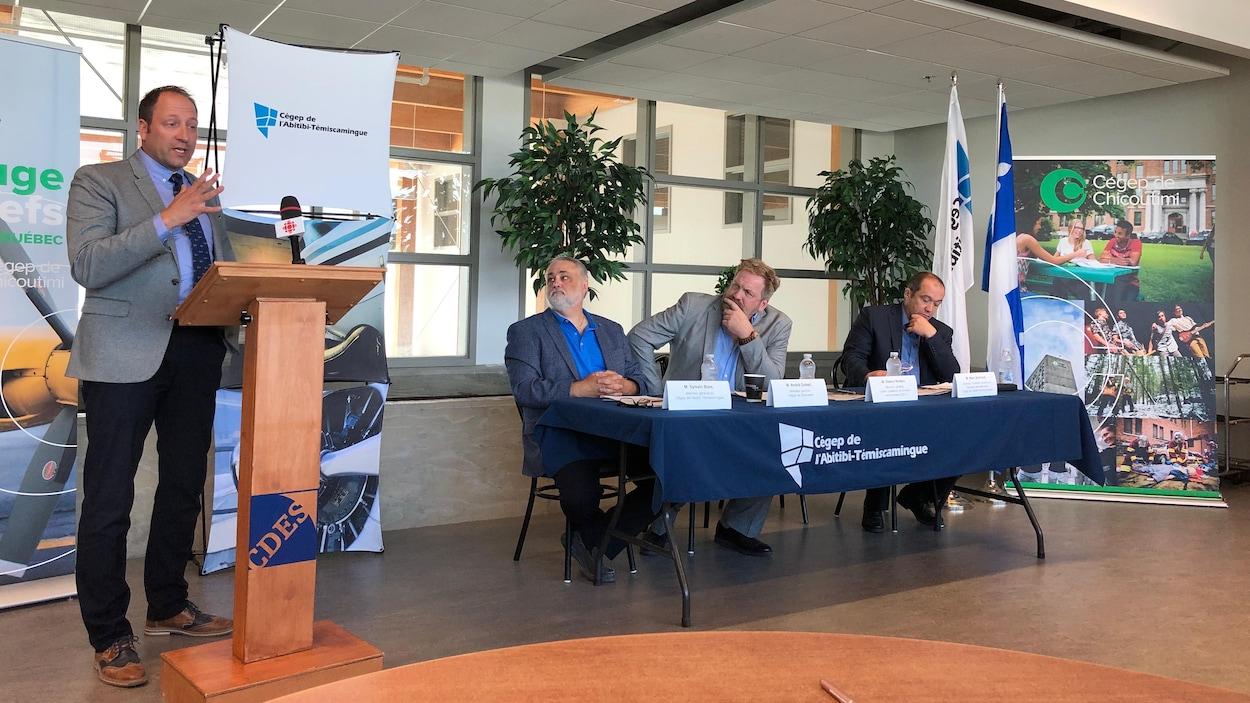 Un homme parle au lutrin pendant que trois hommes assis derrière une table aux couleurs du Cégep de l'Abitibi-Témiscamingue l'écoutent.