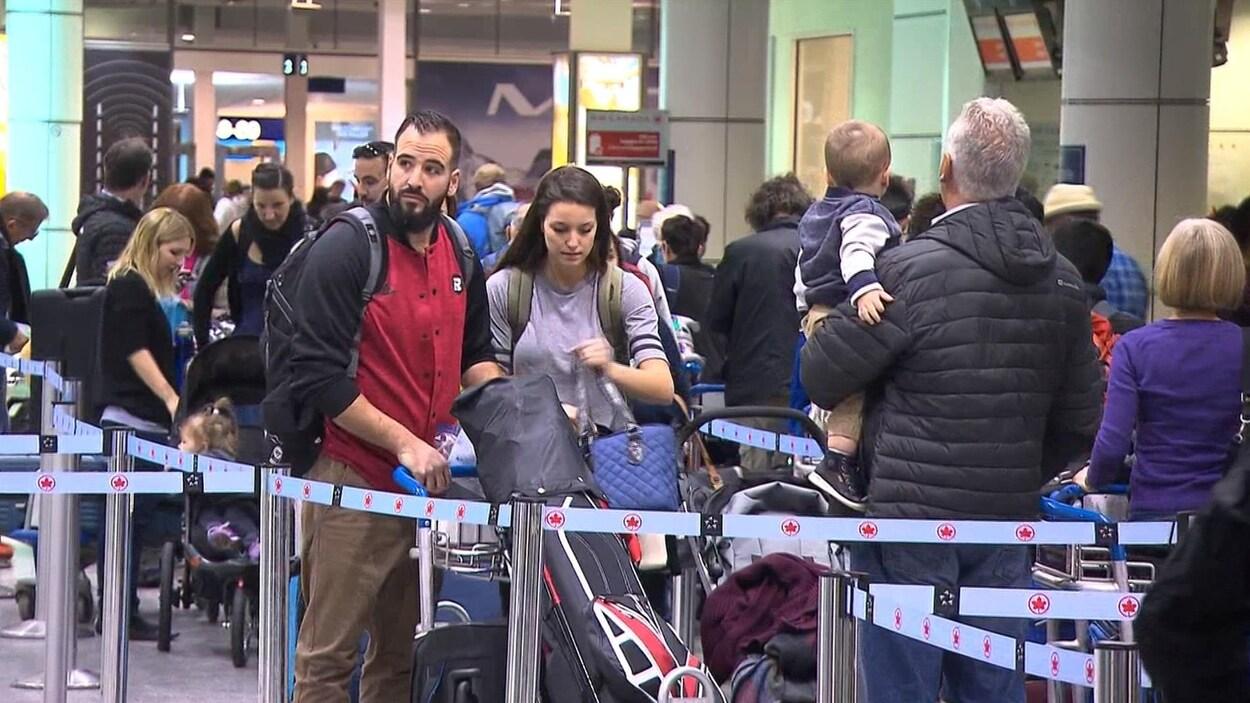 Plusieurs personnes font la file à l'aéroport.